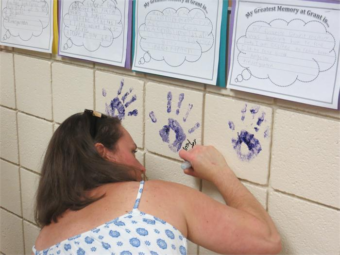 Visitors could add their hand print to the wall of hand prints and sign their name.