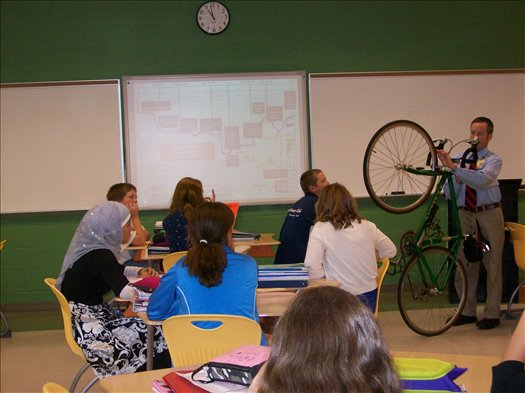 Mr. Costello brings his bike to school to help teach students about distance, rate and circumfrence in Mrs. Kilgore's Math class