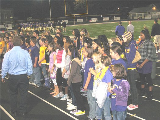 The schools' choirs combine to sing the National Anthem.