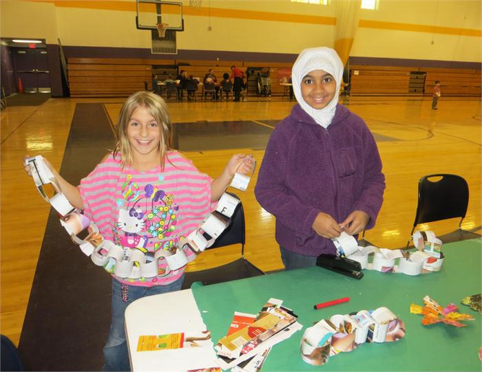 Students show off their crafts made out of recycled materials at the Make and Take station.